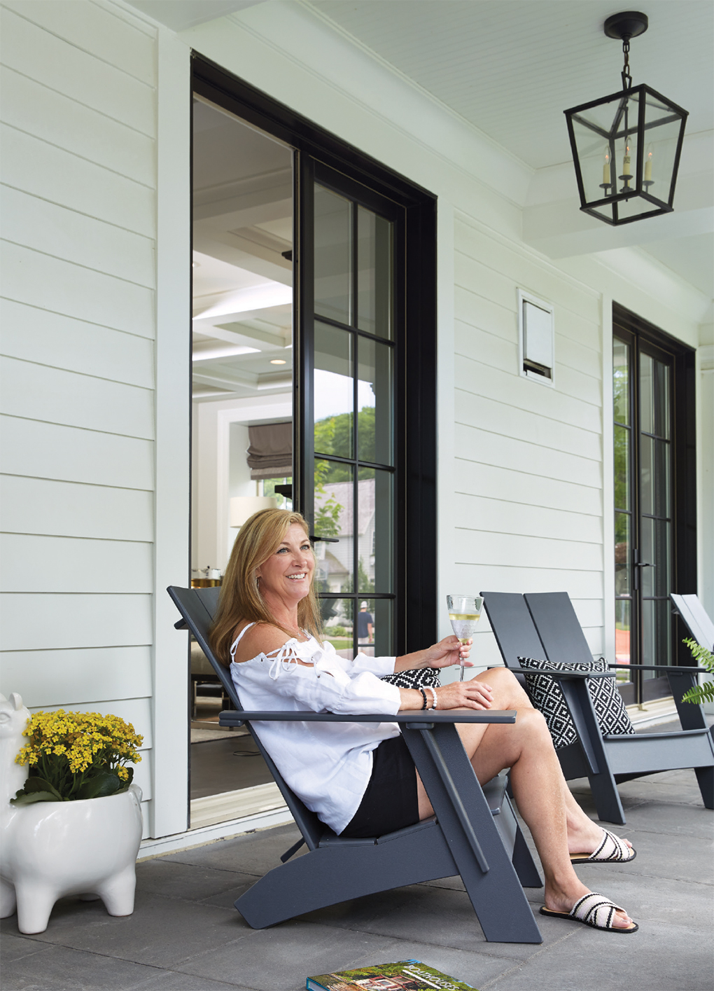 Kathy Nelsen relaxing in a chair on the front porch of her home.