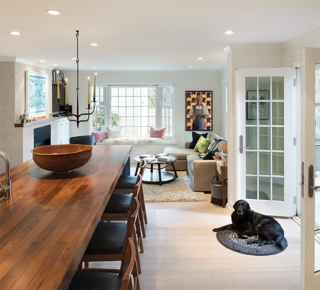 A kitchen leading into a family room. On the floor is a black lab laying on the rug.