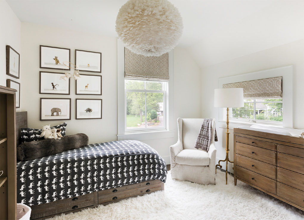 A tan and white bedroom with a small bedroom and framed pictures on the wall.