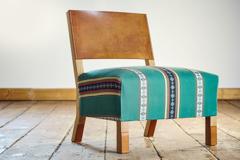 A wooden chair with green cushion.