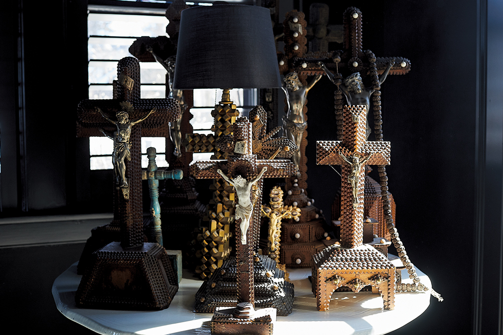 A table displaying a number of intricately carved crucifixes in Christine Ward's, the owner of Patina, home.