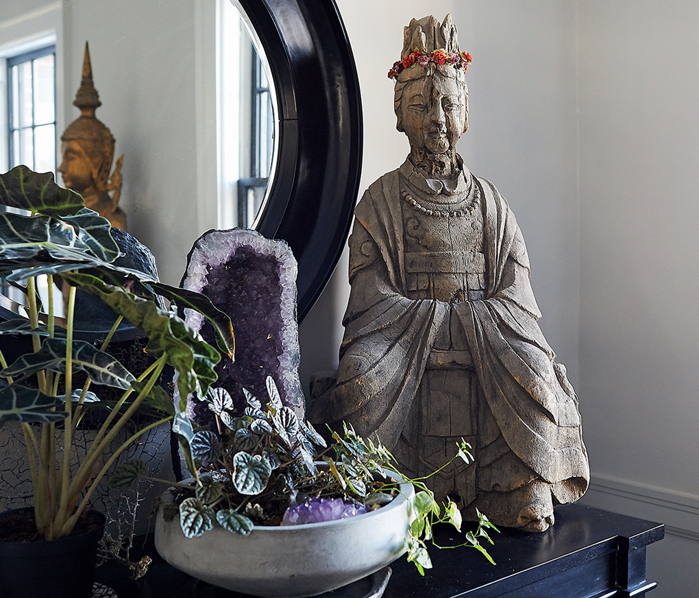 Owner of Patina, Christine Ward, has a table in her home displaying green plants, amethyst geodes and wooden prayer figure next to a mirror.