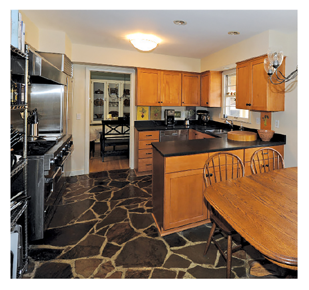 A kitchen with a black stone floor, light wood cabinetry and stainless steel appliances.