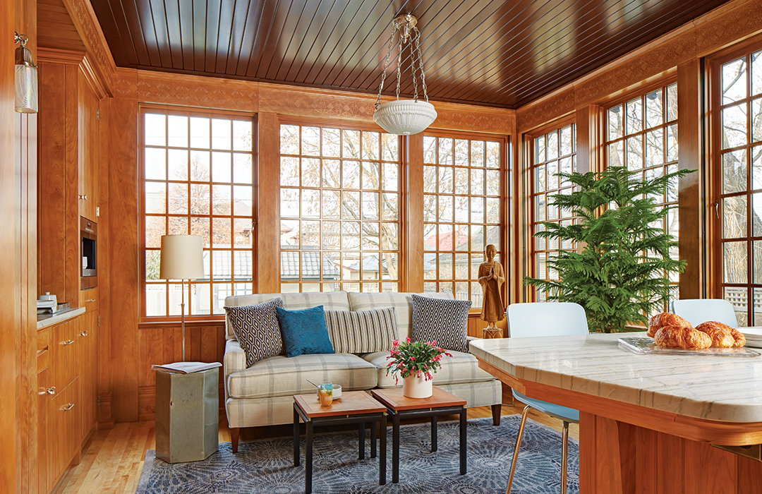 A lounge designed by David Heide Design Studio sits adjacent to the kitchen, and features walls of windows, a fir ceiling, subtle stenciling, and is a favorite spot for the family to gather.