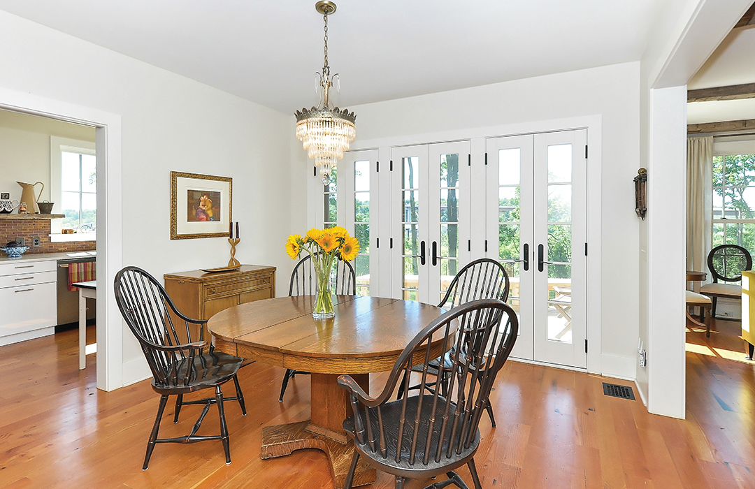 A dining room designed by Studio Hittle features French doors that open onto a balcony overlooking the garden.