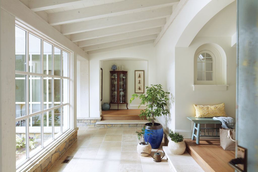 A remodeled home by Albertsson Hansen Architecture features a raftered ceiling, tile floor and large windows.
