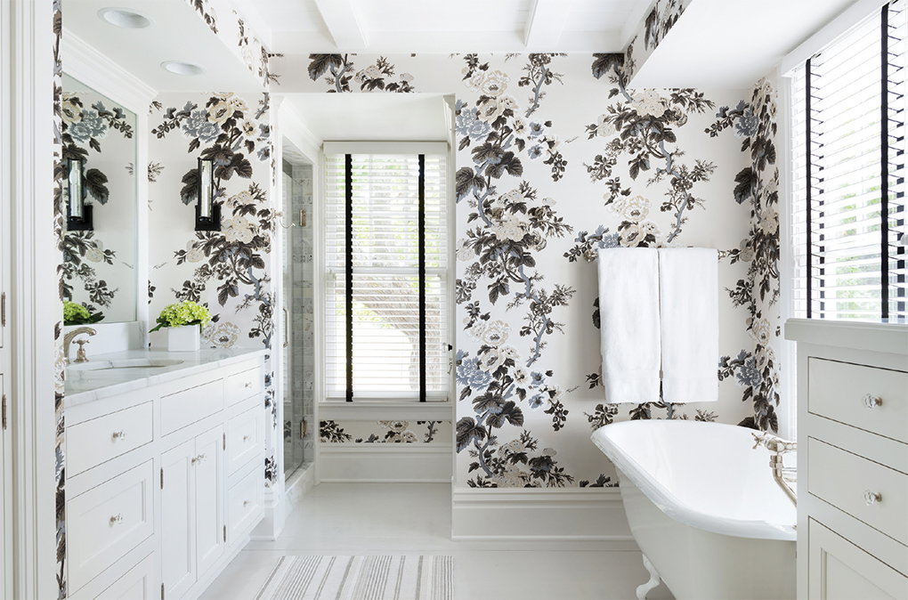 A Lake Minnetonka home with floral wallpaper, white cabinetry, and white soaking tub.