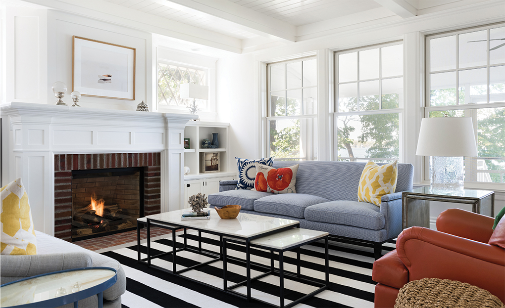 A red brick fireplace in an all white living room in a Lake Minnetonka home.