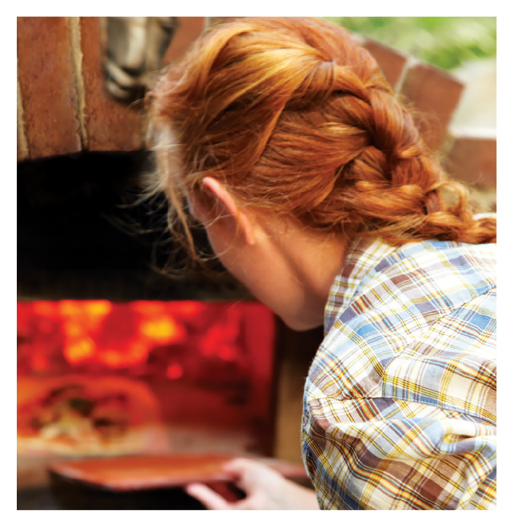 A lady putting a pizza into an outdoor pizza oven.