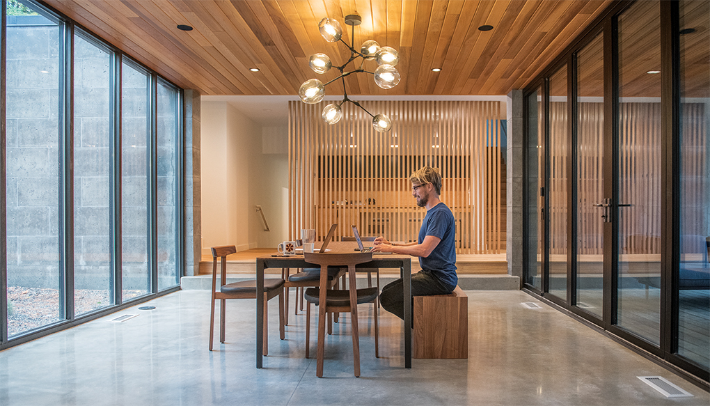 A home designed by Strand Design features a polished concrete floor, floor-to-ceiling windows, and wood tables and chairs.