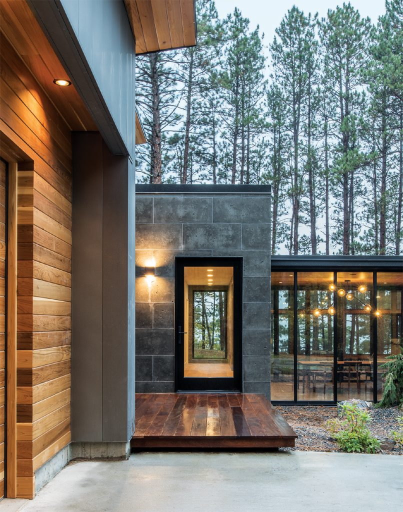 The exterior of a modern home by Strand Design in the north woods.