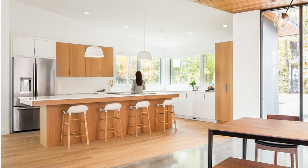 A kitchen designed by Strand Design features rift-sawn white oak cabinetry and white quartz countertops.