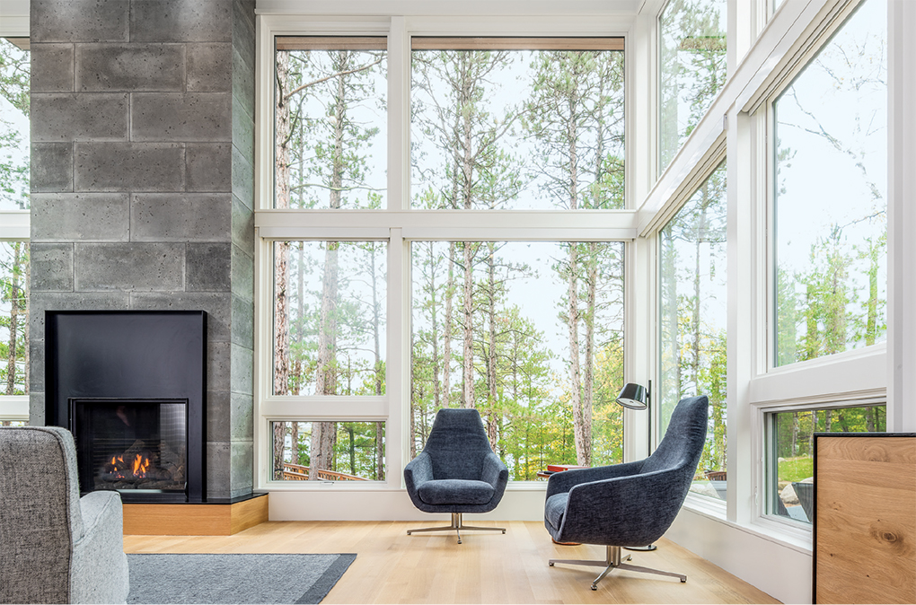 A home designed by Strand Design features a two-story living room with concrete block fireplace.