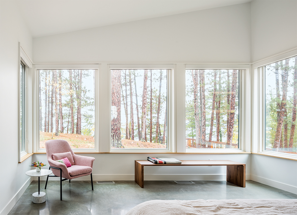 A master bedroom designed by Strand Design features large windows looking out to a forest and a white oak sitting ledge.