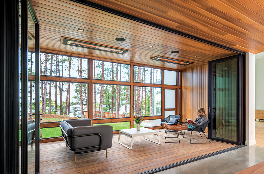 A patio of a modern home by Strand Design features a wall of windows looking out into a forest.