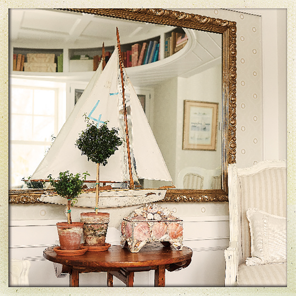 An antique model sailboat rests of a table with a circular bookshelf built into the ceiling above.