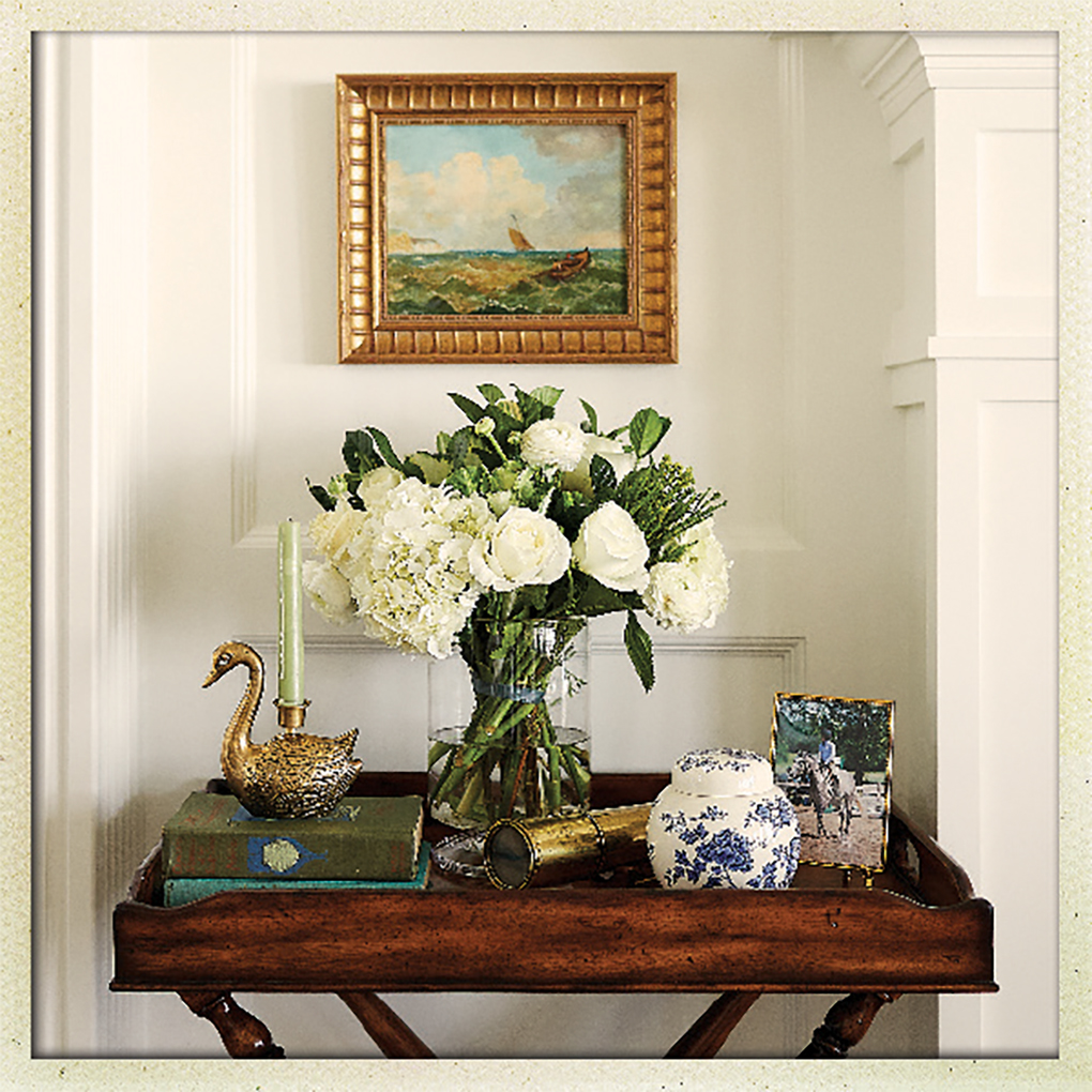 An antique butler table holding a brass swan and vintage spyglass.