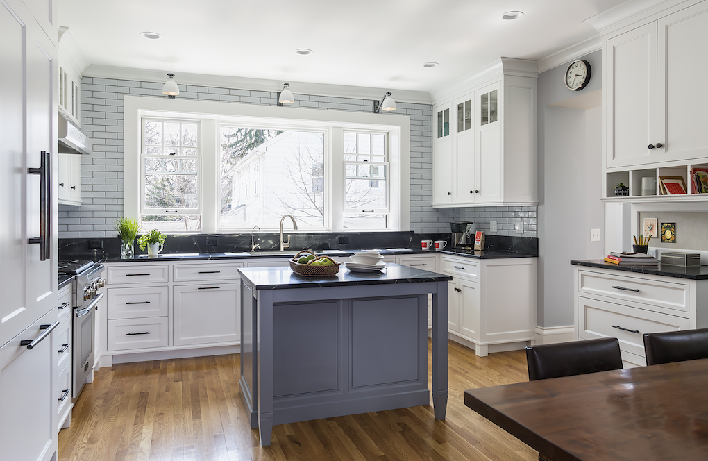 White kitchen with large window and small gray island