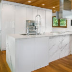Maison kitchen and bath kitchen remodel with wood floors and large white island