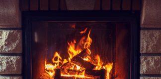 A fire burns inside a stone fireplace.