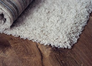 Layered rugs on a brown floor.