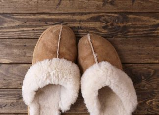 Sheepskin slippers sitting on a wood floor.