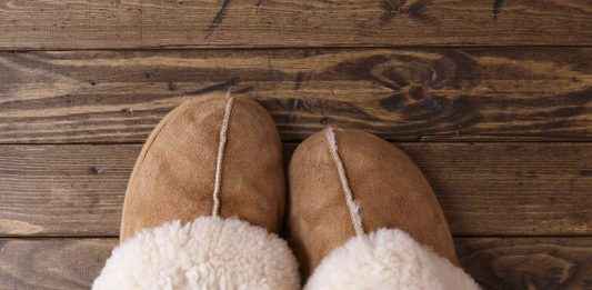 Sheepskin slippers sitting on a wood floor.