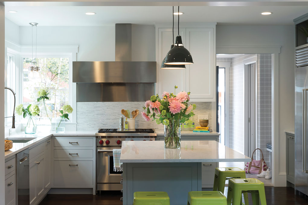 White cabinets surround a silver range hood accented by a marble mosaic. The island is surrounded by lime green stools, and a vase full of pink flowers sits on top.