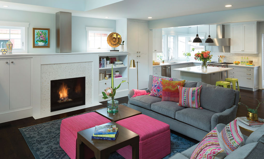 An open living room with fireplace is populated by gray couches and vibrantly-colored pillows. A a modern kitchen with clean lines can be found in the background.