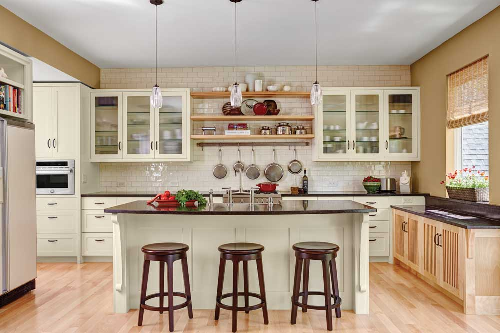 A kitchen designed by Gigi Digiacomo of Digiacomo Homes, Inc. shows light-colored hardwood flooring, white cabinetry, black countertops and an island surrounded by dark-colored wooden stools.