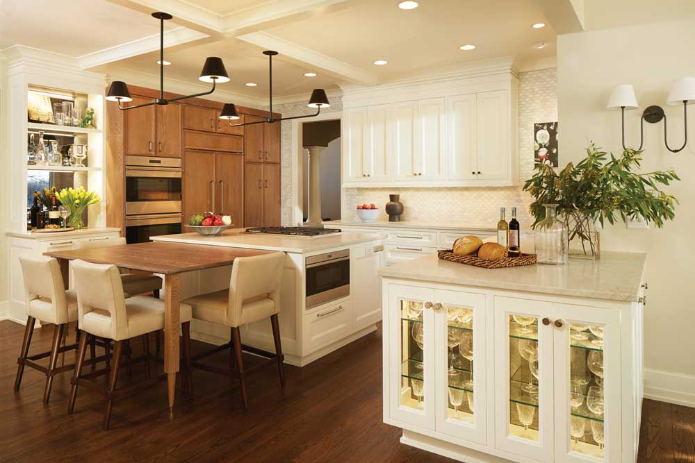 A kitchen in Eden Prairie designed by Linda Engler and Jenn Taft of Engler Studio featured on the 2017 ASID Kitchen Tour. White cabinetry is accented by a light-colored wood dining table with cream-colored counter stools surrounding it.