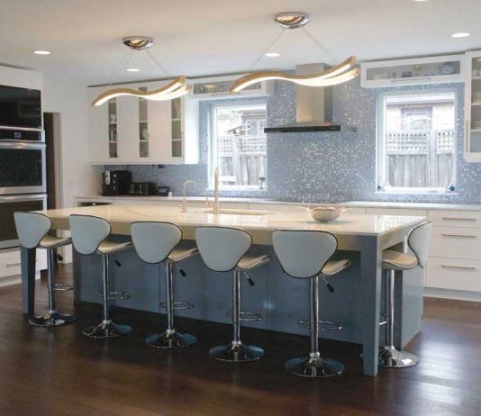 A kitchen designed by Nicole Sirek of Partners 4, Design on the 2017 ASID Kitchen Tour. White cabinetry is accented by a blue-tiled backsplash. In the center of the kitchen is a blue-colored island with a white countertop, and is surrounded by blue stools.