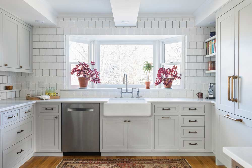 A kitchen designed by Kate Roos of Kate Roos Design, LLC features all white cabinetry and countertops with a white subway tiled backsplash. In the large window over the sink sit two pink flowers.