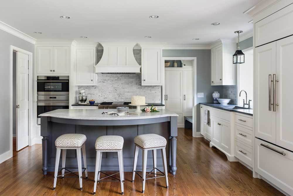 A kitchen designed by Liz Schupanitz Designs on the 2017 ASID Designer Kitchen Tour that features white cabinetry and hardwood floors. In the center is a blue-colored island with stools surrounding it.