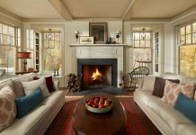A living room designed by Todd Hansen Allied ASID of Alberttson Hansen Architecture that features a cream colored fireplace surrounded by cream colored sofas and a dark wood coffee table with decorative fruit on top.