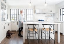 Christine Albertsson stands smiling at the center island of a kitchen she updated in Minneapolis. Her dog, Bruno, is laying on the floor next to her.