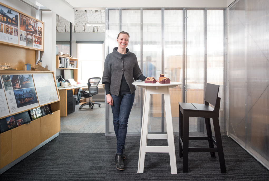 Jody McGuire stands next to white table with a model homes place on top of it in the middle of an office.