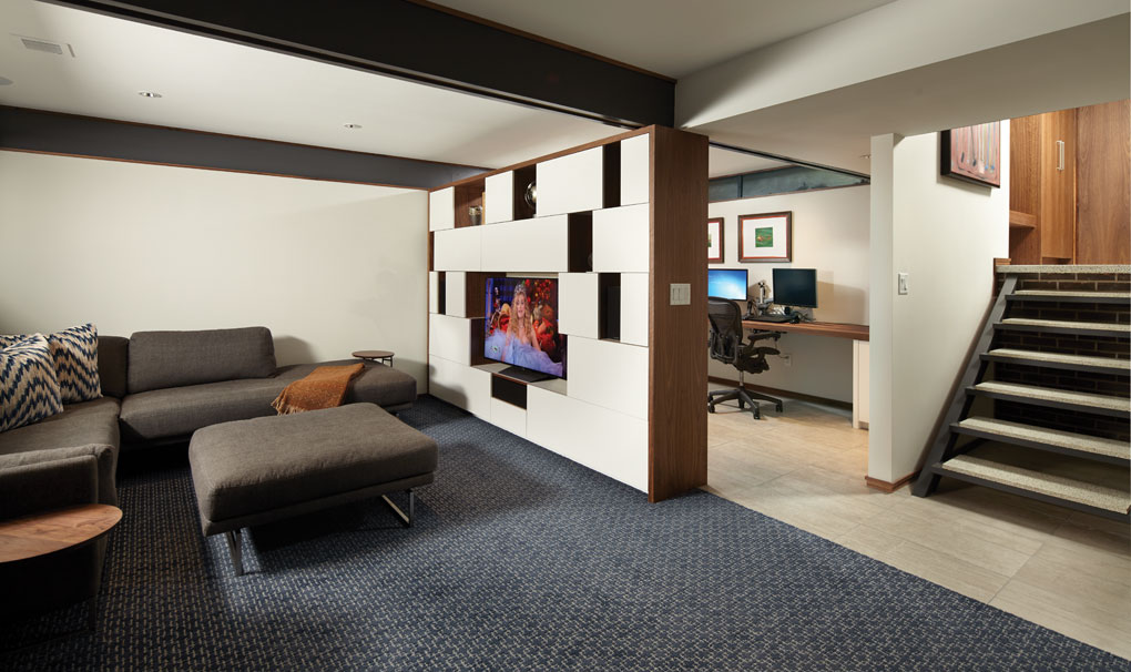A family room with a sofa and footstool is separated from an office by a wall cabinet.