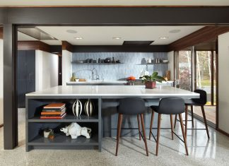 A modern kitchen features a central island with highchairs on one side of it. It also features white countertops, shelves mounted on the ceiling-high backsplash, and a range hood tucked into the ceiling.
