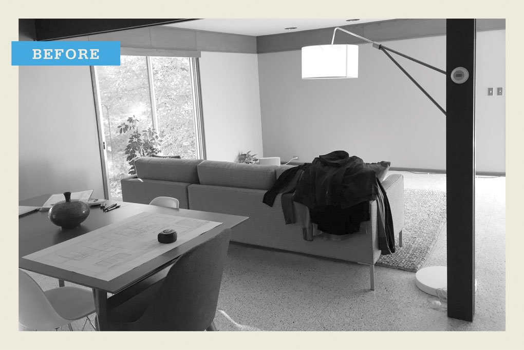 "A black and white ""before"" photo showing a living room with a sofa, table and chairs, and a lamp."