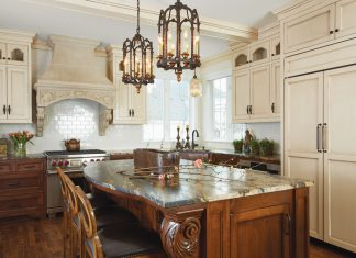 An Italian-styled kitchen shows off carved corbels, a heavily-veined granite, limestone hood hammered copper sink.