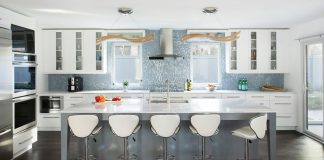 A sleek and modern kitchen with white cabinetry, stainless steel appliances, and an ceiling-height opalescent tile backsplash.