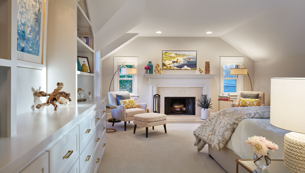 A master bedroom features white bookshelves, fireplace, and chair with accompanying footstool.