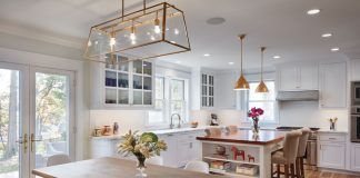 A remodeled kitchen gives a modern feel and features hardwood flooring, white cabinetry, and a wrought-iron chandelier of the dining table.