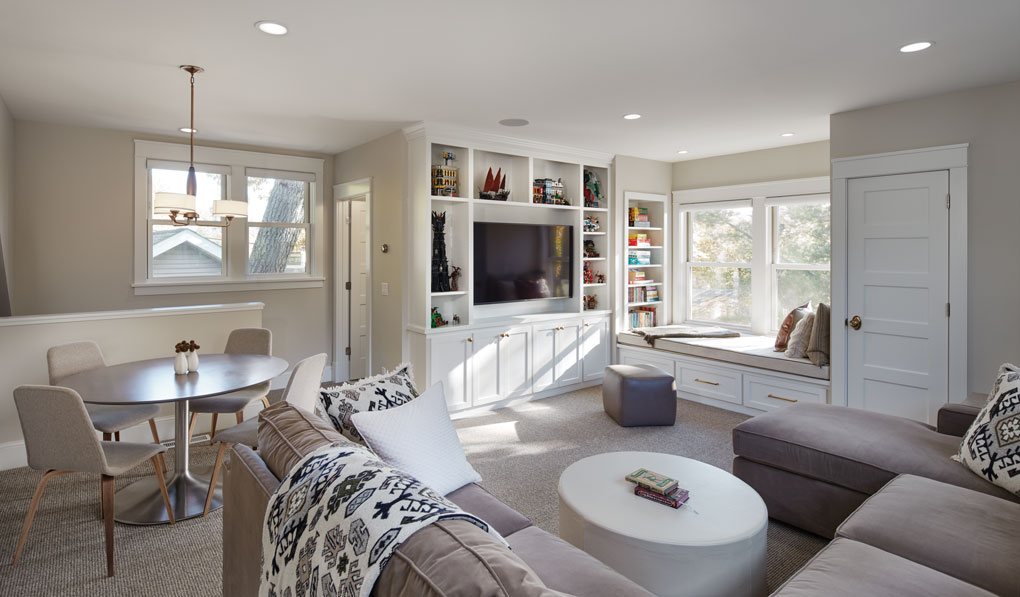 A guest suite above an attached garage features a wraparound sofa with footstool, small table and chairs, and a white entertainment shelf.