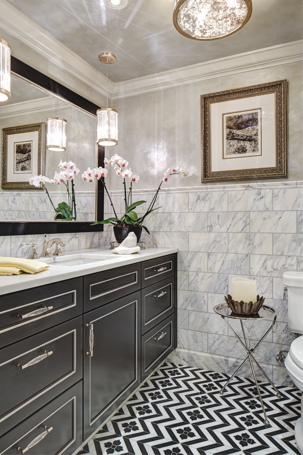 A bathroom with a sophisticated neutral color palette features tiled floor, marble walls, and chandeliers over the vanity.