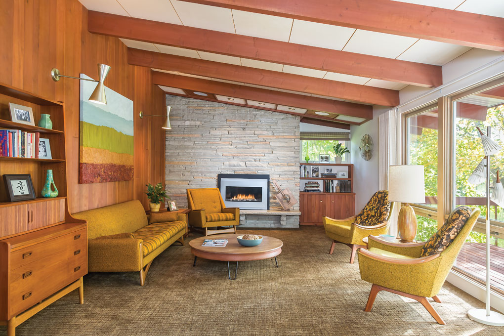 Living room of mid-century house with cherry paneling and vaulted ceilings and exposed beams.