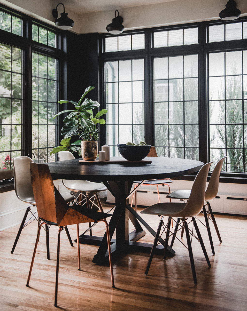 A dining room table is surrounded by unlacquered copper chairs. Behind them are large windows.