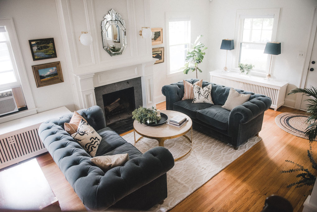 A living room designed by Victoria Sass shows Chesterfield-style sofas flanking a coffee table that is set next to a fireplace.