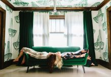 Jennifer Jorgensen and Kate Worum of She She lie on a green couch in a room covered in wallpaper featuring hand drawn chandeliers.